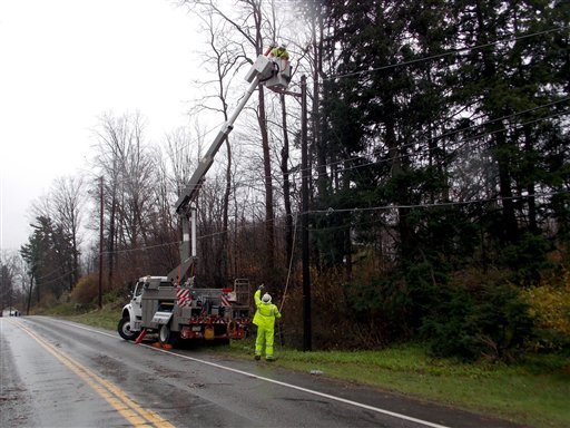 Utility workers make repairs on Tuesday, Oct. 30, 2012, along Route 14 in Canton, Pa., in the aftermath of Sandy. (AP Photo/The Daily Review, Eric Hrin)