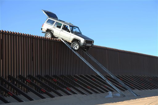 In this photo provided by the U.S. Customs and Border Protection, a silver Jeep Cherokee that suspected smugglers were attempting to drive over the U.S.-Mexico border fence is stuck at the top of a makeshift ramp early Wednesday, Oct. 31, 2012 near Yuma.