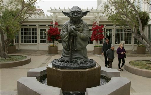 People walk past a fountain showing the Yoda character from the Star Wars movies outside of Lucasfilms headquarters in San Francisco, Tuesday, Oct. 30, 2012. The Walt Disney Co. announced Tuesday that it was buying Lucasfilm Ltd. for $4.05 billion. (AP)