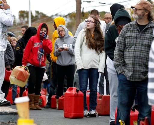 © As temperatures begin to drop, people wait in line to fill containers with gas at a Shell gasoline filling station Thursday, Nov. 1, 2012, in Keyport, N.J. In parts of New York and New Jersey, drivers lined up Thursday for hours at gas stations.
