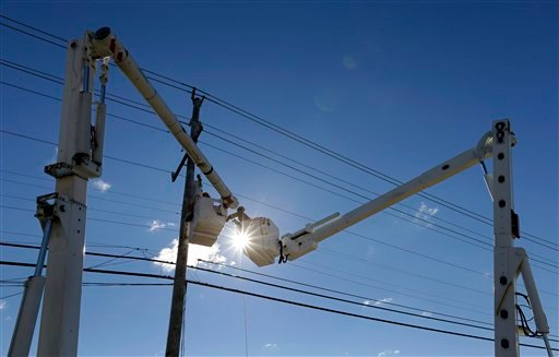 © A utility crew works to restore power on Long Beach Island, N.J., Saturday, Nov. 3, 2012, after communities on the island sustained damage from Superstorm Sandy.