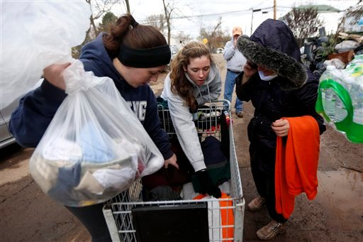 © Volunteers Laurie McLoughlin, left, and her sister Caitlin McLaughlin, center, sort through clothing to donate to a resident, Saturday, Nov. 3, 2012, in Staten Island, N.Y.