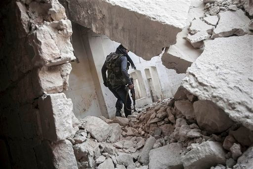 © In this Friday, Nov. 02, 2012 photo, a rebel fighter walks among the debris of damaged residential buildings after several days of intense fighting between rebel fighters and the Syrian army in the Karm al-Jebel neighborhood in Aleppo, Syria.