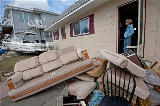 © Justin Thompson, 9, looks over his family's ruined furniture and the boat that landed on their lawn on Nov. 1, 2012 in Brigantine, N.J. Frustration is setting in for some New Jersey residents who are still without power and running low on food.