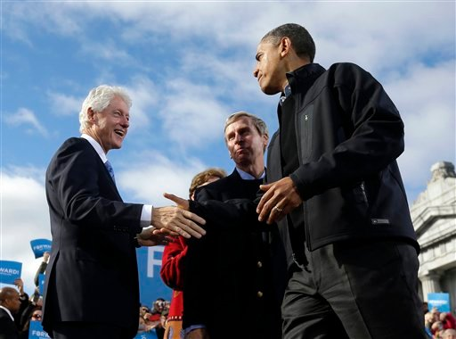 © President Barack Obama, right, shakes hands with former President Bill Clinton, left, as New Hampshire Gov. John Lynch, center, watches on stage together during a campaign event at Capitol Square, Sunday, Nov. 4, 2012, in Concord, N.H.
