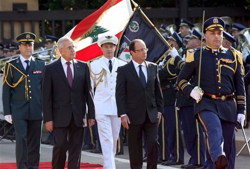© In this photo released by Lebanon's official government photographer Dalati Nohra, Lebanese President Michel Suleiman, second left, and French President Francois Hollande, second right, review honor guards, at the Presidential Palace in Baabda.