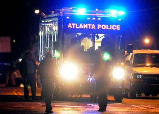 © Law enforcement personnel investigate the scene of an Atlanta Police Department helicopter crash early Sunday, Nov. 4, 2012, that killed two officers aboard the aircraft when it crashed near a shopping center late Saturday, Nov. 3, 2012.