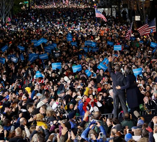 © President Barack Obama and first lady Michelle Obama wave to supporter during the final 2012 campaign event in downtown Des Moines, Iowa, Tuesday, Nov. 6, 2012.