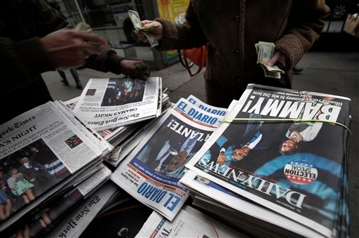 A news dealer sells copies of his papers on New York's Upper West Side, Wednesday, Nov. 7, 2012. (AP Photo/Richard Drew)