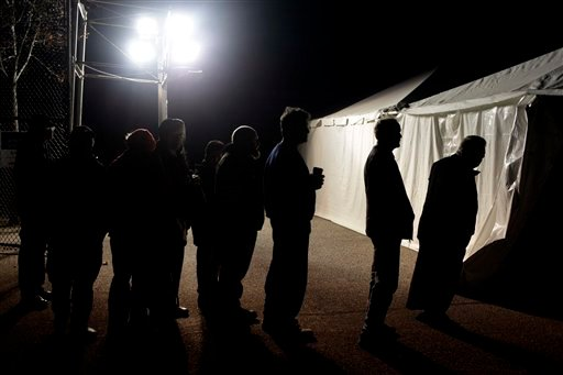 © Under the lights of a generator, voters wait in line outside of a tent serving as a polling site in the Midland Beach section of Staten Island, New York, on Election Day Tuesday, Nov. 6, 2012.
