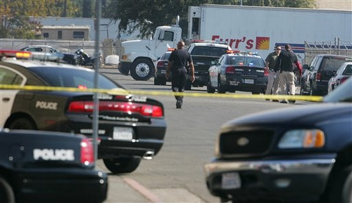 © Police search an area where a workplace shooting occurred that killed one person and wounded several others at Valley Protein, formally known as Apple Valley Farms Tuesday, Nov. 6, 2012, in Fresno, Calif.