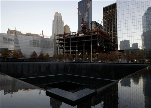 © Surrounding buildings are seen in one of the two reflecting pools at the World Trade Center Memorial where water running again after it had been shut down due to flooding in the wake of Superstorm Sandy, Monday, Nov. 5, 2012, in New York.