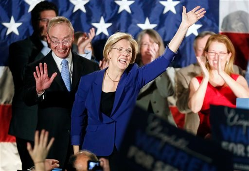 Democrat Elizabeth Warren, center, waves to the crowd with her husband Bruce Mann, left, during an election night rally at the Fairmont Copley Plaza hotel in Boston after Warren defeated incumbent GOP Sen. Scott Brown in the Massachusetts Senate race. (AP