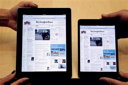 FILE -In this Friday, Nov. 6, 2012, file photo, employees hold a new full size Apple iPad 4th generation, left, next to new Apple iPad mini at the Apple store on Michigan Ave. (AP Photo/M. Spencer Green)