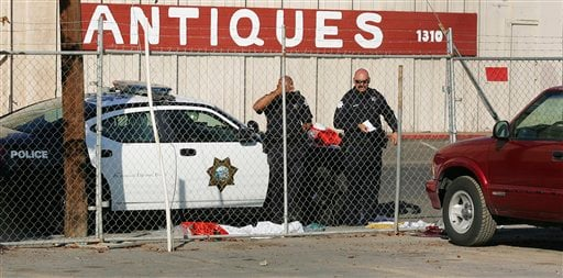 Fresno police officers look over the area where a man killed himself after shooting people in his workplace at Valley Protein, formally known as Apple Valley Farms Nov. 6, 2012 in Fresno, Calif.(AP Photo/Gary Kazanjian)