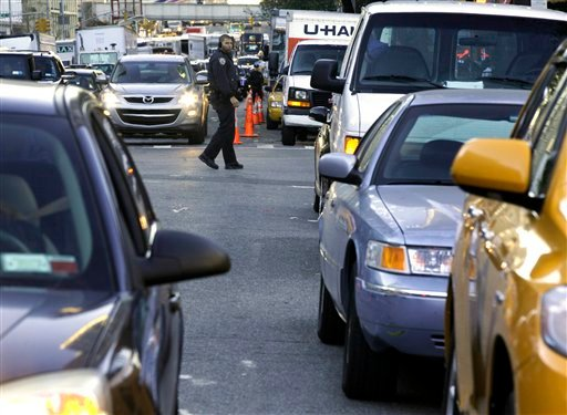 New York City Police Department officers manage the line of cars waiting for gasoline, in New York, Friday, Nov. 9, 2012.  (AP Photo/Richard Drew)