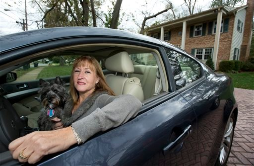 In this photo taken Nov. 2, 2012, Diane Spitaliere and her pet dog Izzie sit in her car outside her house in Alexandria.  (AP Photo/Manuel Balce Ceneta)