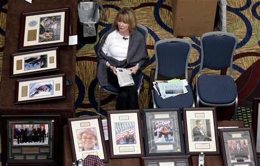 © This Feb. 24, 2012 file photo shows Kay Aaron waiting for customers at a booth selling pictures of Republican leaders and icons during the California Republican Party convention in Burlingame, Calif.