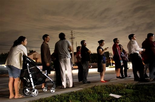 © This Nov. 6, 2012 file photo shows voters lined up in the dark to beat the 7:00 p.m. deadline to cast their ballots at a polling station in Miami. It's not just the economy.
