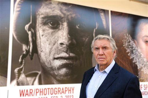 © In this Thursday, Nov. 8, 2012 photo, photographer Don McCullin poses in front of the Houston Museum of Fine Arts' sign promoting the new War/Photography exhibit in Houston.