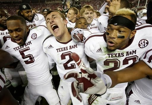 © Texas A&M quarterback Johnny Manziel (2) is joined by wide receiver Kenric McNeal (5) and defensive back Dustin Harris (22) as they celebrate after the Aggies defeated top-ranked Alabama 29-24 in an NCAA college football game at Bryant-Denny Stadium.