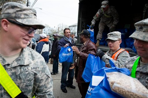 © New York Governor Andrew Cuomo assists the National Guard unload a truck of supplies in the Far Rockaways section of the Queens borough of New York, Saturday, Nov. 10, 2012.