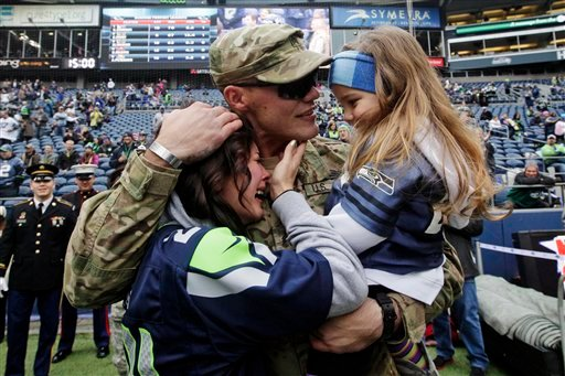 © United States Army Sgt. Zach Ames, center, who has been on a one-year deployment to Afghanistan, surprises his wife, Bri Ames and their daughter Emersyn, with a reunion prior to an NFL football game between the New York Jets and the Seattle Seahawks.