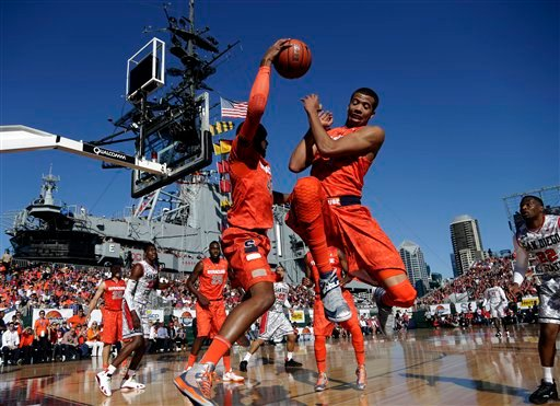 © Syracuse forward James Southerland, left, saves a ball from going out of bounds as Michael Carter-Williams, right, jumps out of the way while playing San Diego State during the first half of an NCAA college basketball game on the deck of the USS Midway.