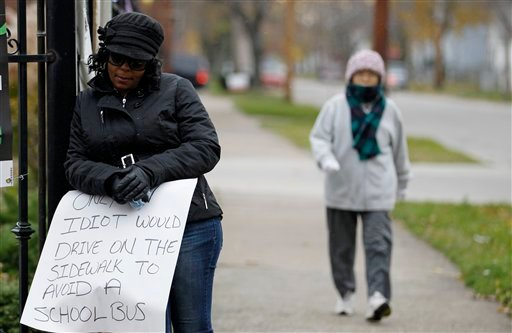 A woman walks by as Shena Hardin, left, holds up a sign to serve a highly public sentence Tuesday, Nov. 13, 2012, in Cleveland. (AP Photo/Tony Dejak)
