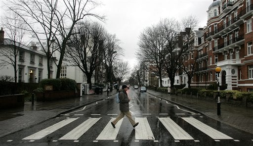 "© In this file photo taken Feb. 16, 2010, a man walks on the zebra crossing made famous from the album cover of The Beatles' ""Abbey Road"" in front of Abbey Road Studios, seen at left, in London."