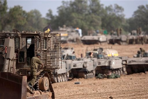 © Israeli soldiers work on their a tanks in a staging ground near the border with Gaza Strip, southern Israel, Friday, Nov. 16, 2012. Fierce clashes between Israeli forces and Gaza militants are continuing for the third day.