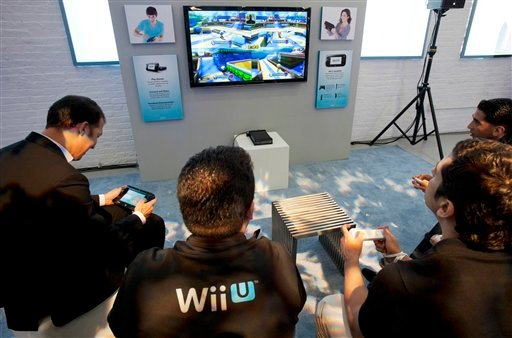 ©  In this Thursday, Sept. 13, 2012 file photo, people demonstrate the Nintendo's Wii U GamePad and console in New York. Nintendo seeks to shake up gaming again with the Wii U touchscreen controller.