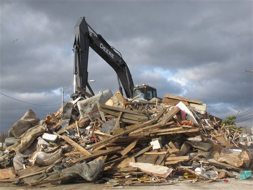A crane sits atop a pile of storm debris in a parking lot in Point Pleasant Beach N.J. on Nov. 15, 2012. (AP Photo/Wayne Parry)