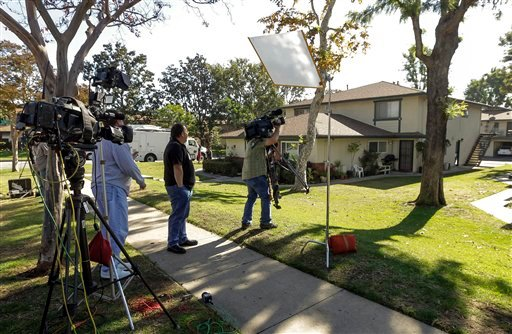 Members of the media gather outside the home of 21-year-old Miguel Alejandro Santana Vidriales of Upland, Calif. Tuesday, Nov. 20, 2012. (AP Photo/Damian Dovarganes)