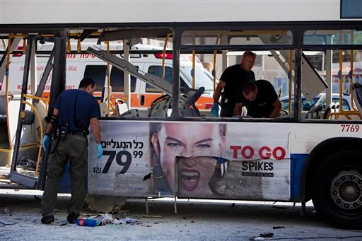 Israeli police officers examine a blown up bus at the site of a bombing in Tel Aviv, Israel, Wednesday, Nov. 21, 2012. (AP Photo/Oded Balilty)