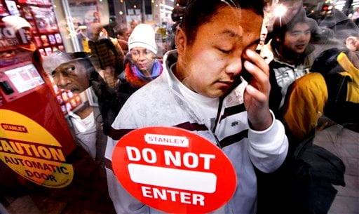 FILE - In this Friday, Nov. 28, 2008, file photo, Frankie Lee, the first in a line of several hundred shoppers at a Wal-Mart in Oakland, Calif., rubs his eyes shortly before the store opens at 5 a.m. (AP Photo/Noah Berger)
