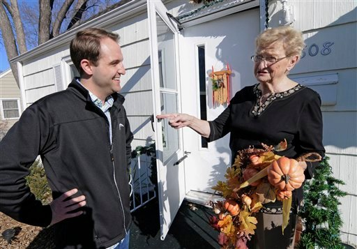 Jake Loesch and his grandmother, Bunny Arseneau pose outside Bunny's home where they replaced the Thanksgiving ornament with one for Christmas on the front door, Tuesday, Nov. 20, 2012 in Crystal, Minn. (AP Photo/Jim Mone)