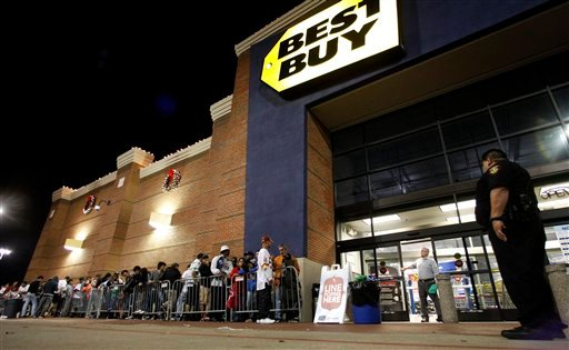 © Tarrant County Sheriffs Deputy Nick Downs, right, watches a line of shoppers as Best Buy general manager Shaun Ogdie, standing at door, peers outside as he and his employees prepare to open at midnight Thursday Nov. 22, 2012, in Arlington, Texas.
