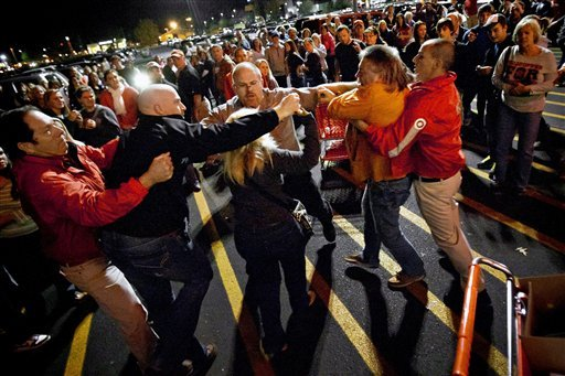 A crowd gathers as security guards break up a fight between shoppers waiting in line just as the doors open for Black Friday shopping at Target, Thursday, Nov. 22, 2012, in Bowling Green, Ky. (AP Photo/Daily News, Alex Slitz)