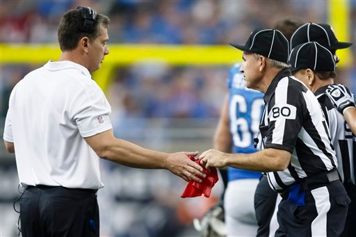 Field judge Greg Gautreaux (80) hands the red challenge flag back to Detroit Lions head coach Jim Schwartz in the first half of an NFL football game against the Houston Texans at Ford Field in Detroit Nov. 22, 2012. (AP Photo/Rick Osentoski)