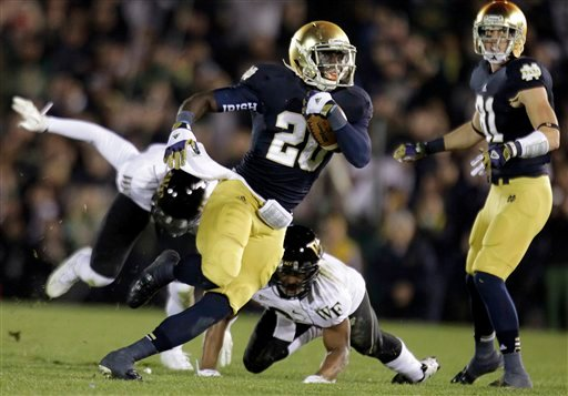 © Notre Dame running back Cierre Wood (20) cuts around Wake Forest defenders as he picks up 42 yards during the second half of an NCAA college football game in South Bend, Ind., Saturday, Nov. 17, 2012. Notre Dame defeated Wake Forest 38-0.