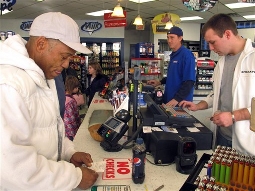© Michael Arrington, left, buys a Powerball ticket from cashier Lee Heilig, right, on Friday, Nov. 23, 2012, at a DeliMart convenience store in Iowa City, Iowa. The jackpot had reached $325 million as of Friday.