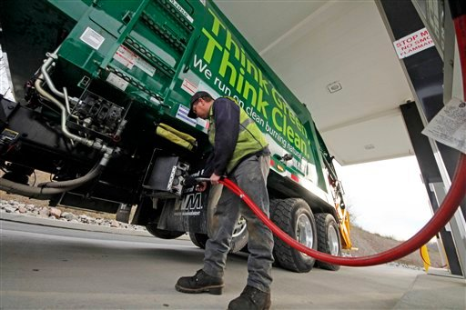 © In this Nov. 19, 2012 photo, Waste Management driver Alan Sadler fills his truck with CNG gas at the company's filling station in Washington, Pa.