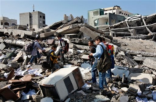 © Palestinian school children walk in the rubble left days after an Israeli strike destroyed the Hamas interior ministry in Gaza City, Monday, Nov. 26, 2012.