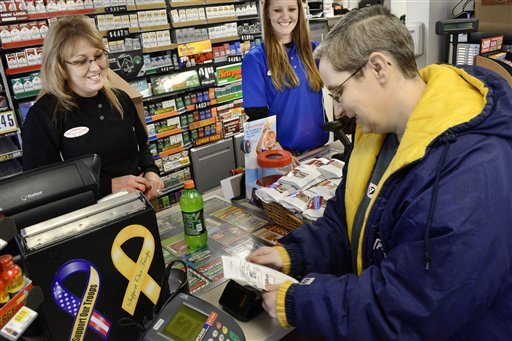Manager Julie Rebennack, left, and customer service representative Megan Horn wish Lori Soule, 48, right, good luck after Soule purchased a Powerball ticket Monday, Nov. 26, 2012, at a Speedway convenience store in Marion, Ind. (AP Photo/The Chronicle-Tri