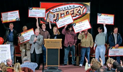 In this Feb. 22, 2006, file photo, the eight winners of the $365 million Nebraska Powerball lottery hold up their ceremonial checks at a news conference in Lincoln, Neb. (AP Photo/Nati Harnik, File)