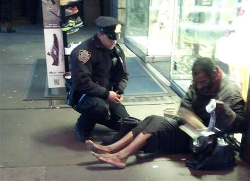 This photo provided by Jennifer Foster shows New York City Police Officer Larry DePrimo presenting a barefoot homeless man in New York's Time Square with boots Nov. 14, 2012. (AP Photo/Jennifer Foster)