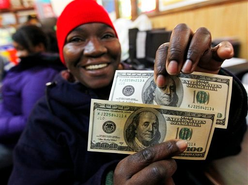Charlotte Muhammad holds up two $100 dollar bills she got from Secret Santa, at St. Joseph's Social Service Center in Elizabeth, N.J.