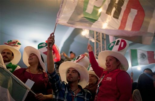In this July 1, 2012 file photo, supporters of Enrique Pena Nieto, presidential candidate for the Revolutionary Institutional Party (PRI) gather at party headquarters as exit polls begin to come in for general elections in Mexico City, Mexico.