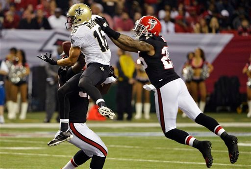 New Orleans Saints wide receiver Lance Moore (16) makes a catch between Atlanta Falcons' Sean Weatherspoon, obscured, and Charles Mitchell (26) during the first half of an NFL football game, Thursday, Nov. 29, 2012, in Atlanta.
